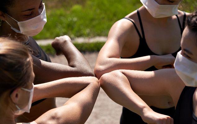 Eine Gruppe Frauen begrüßt sich mit den Ellbogen. Sie tragen dabei medizinische Masken.